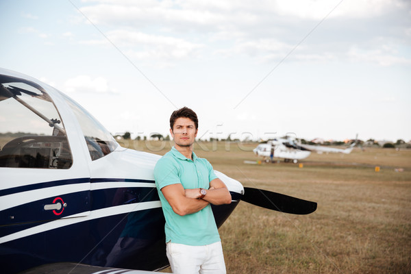 Serious man standing with arms crossed near small plane Stock photo © deandrobot