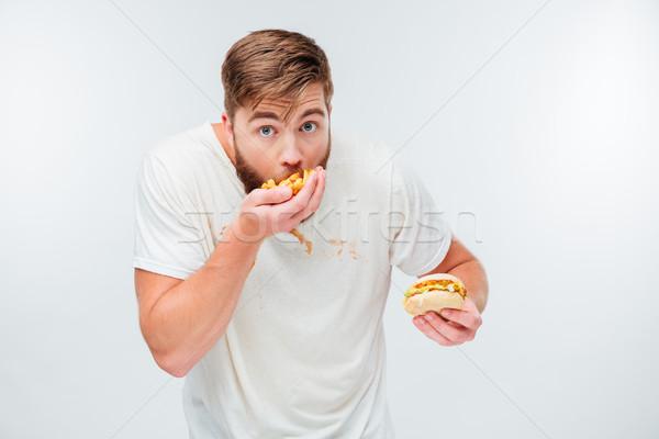 Vicces éhes szakállas férfi eszik egészségtelen étel Stock fotó © deandrobot