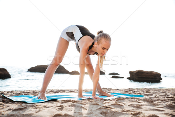 Peaceful young woman doing relaxing yoga exercises stock