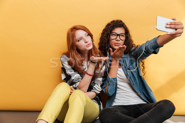 Two women sending kiss and making selfie with mobile phone Stock photo © deandrobot