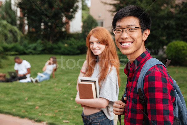 Smiling asian young man student walking with her girlfriend outdoors Stock photo © deandrobot