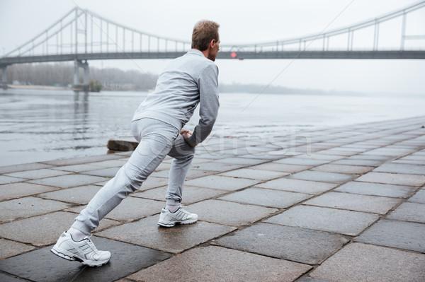 Full length runner warming up near the water Stock photo © deandrobot