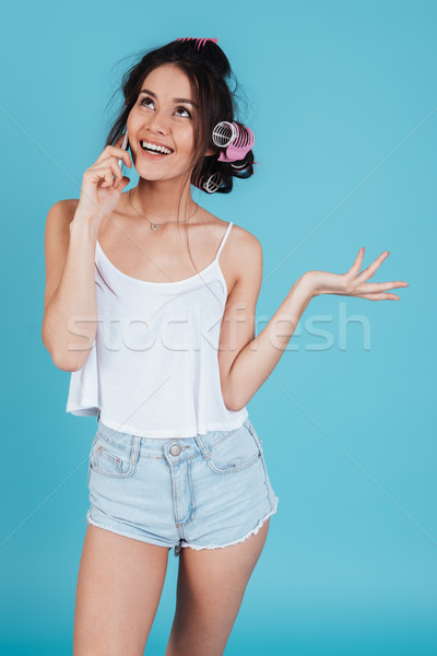 Cheerful young lady talking by phone Stock photo © deandrobot