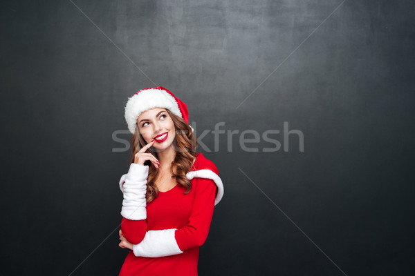 Beautiful wondered woman in red dress and hat looking away Stock photo © deandrobot