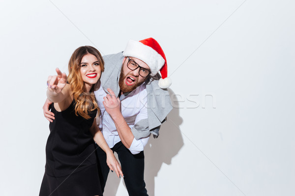 Happy drunk young couple in santa hat standing and shouting Stock photo © deandrobot