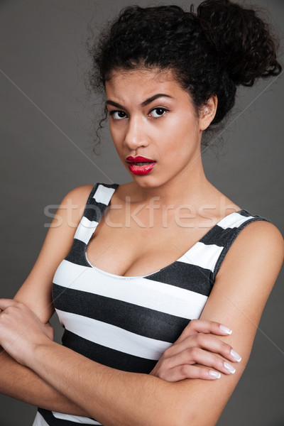 Angry frowning african american young woman standing with arms crossed Stock photo © deandrobot