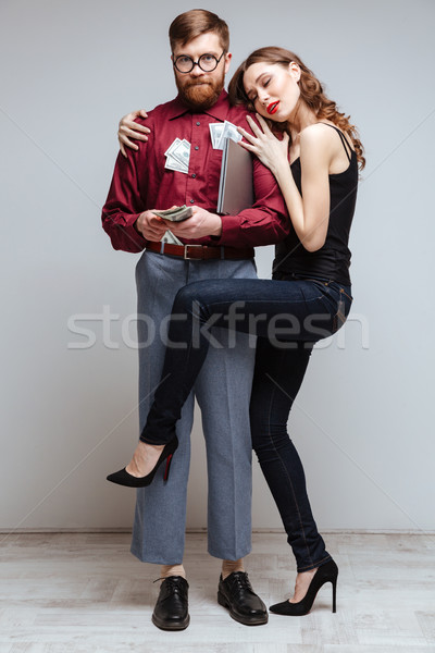 Stock photo: Vertical image of Woman stick to Male nerd with money