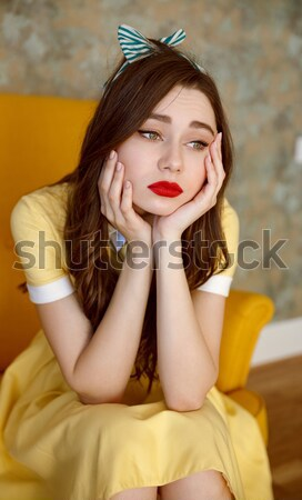 Stock photo: Cute pin up girl in yellow dress sitting in chair