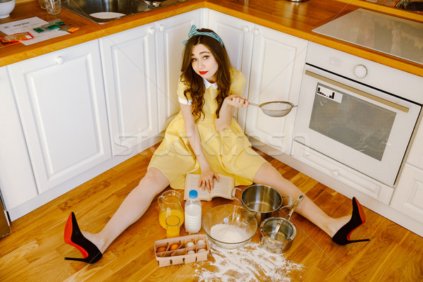 Beautiful pin-up woman sitting on floor and cooking Stock photo © deandrobot