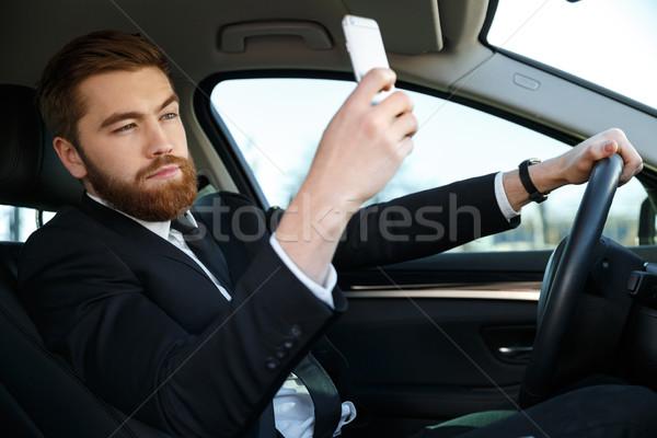 Vue de côté calme homme d'affaires costume téléphone Photo stock © deandrobot