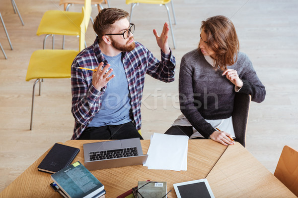 Angry students sitting in library while quarrel. Stock photo © deandrobot