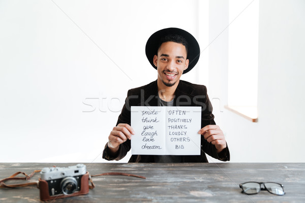 African man holding sheet of paper with words Stock photo © deandrobot
