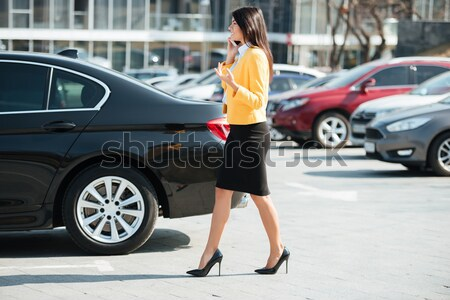 Legs of businesswoman with high heels shoes walking near car Stock photo © deandrobot