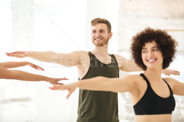 Mixed group of fitness people doing exercises Stock photo © deandrobot