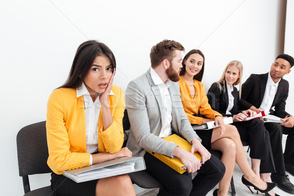 Confused lady sitting near colleagues in office Stock photo © deandrobot