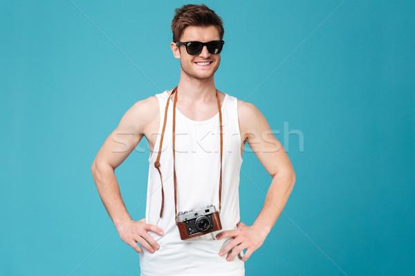 Homme lunettes de soleil posant isolé bleu photo Photo stock © deandrobot