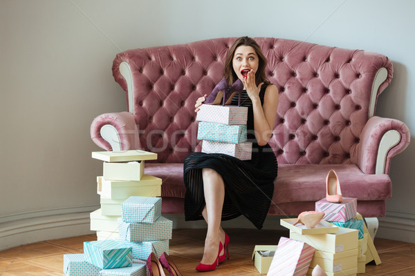 Smiling young lady sitting on sofa indoors choosing shoes. Stock photo © deandrobot