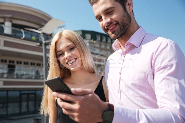 Stock photo: Smiling young couple using mobile phone