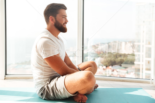 Side view of Smiling bearded man doing yoga exercise Stock photo © deandrobot
