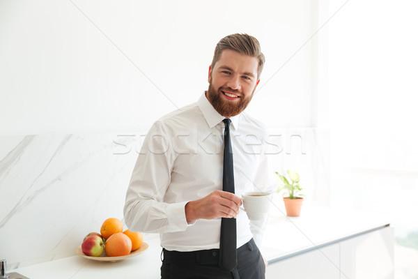 Sorridente barbudo homem de negócios potável café cozinha Foto stock © deandrobot