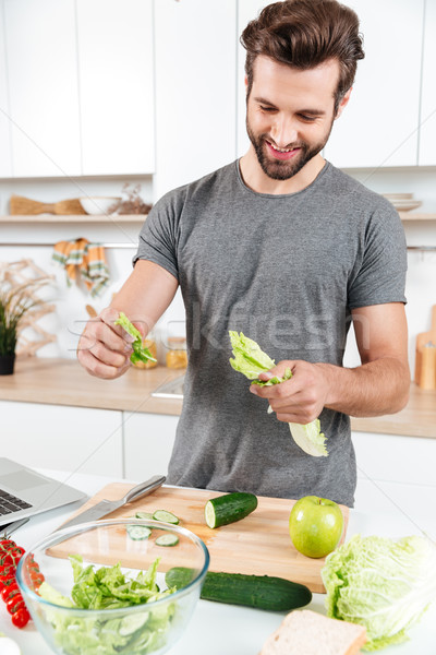 Happy handsome guy cooking salad with laptop Stock photo © deandrobot