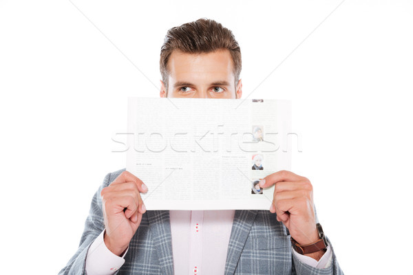 Serious young man standing isolated holding gazette Stock photo © deandrobot