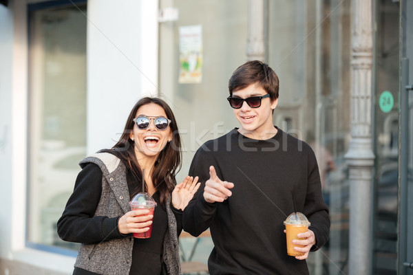 Happy young lady walking outdoors with her brother Stock photo © deandrobot