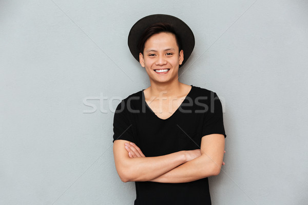 Cheerful young asian man standing over grey background Stock photo © deandrobot