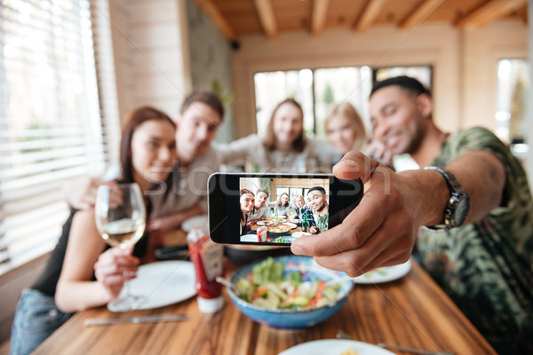 Group of friends having dinner and taking selfie with smartphone Stock photo © deandrobot