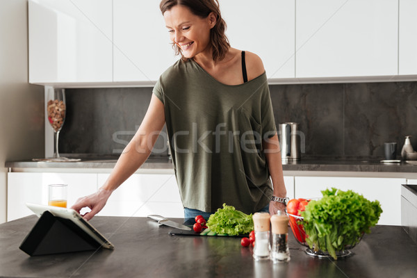 Smiling casual woman standing near the table with vegetables Stock photo © deandrobot