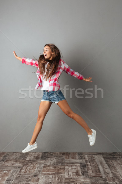 Full-length photo of pretty young woman in checkered shirt jumpi Stock photo © deandrobot