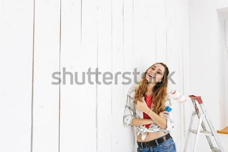 Photo of happy young woman wearing checkered shirt and blue jean Stock photo © deandrobot