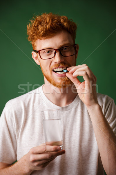 Portrait of a young redhead man in eyeglasses biting pill Stock photo © deandrobot