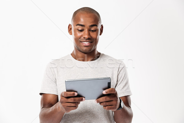 Smiling african man using tablet computer Stock photo © deandrobot