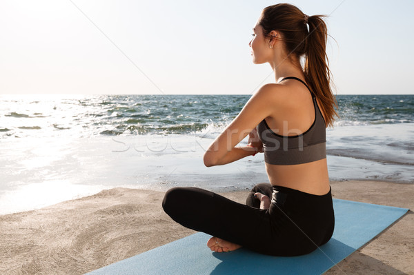 Charming young woman practicing yoga at the seaside Stock photo © deandrobot