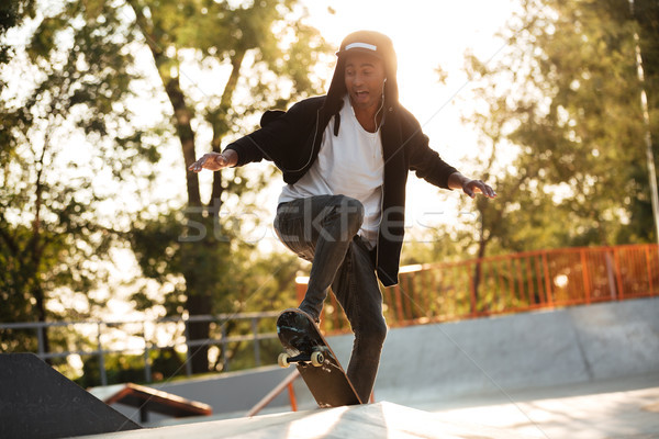 Afro american guy jumping with his skate Stock photo © deandrobot
