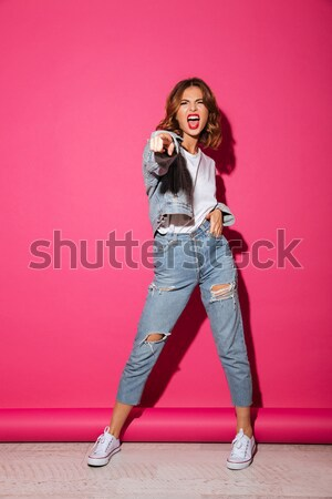 Full-length image of smiling brunette woman posing with crossed arms Stock photo © deandrobot