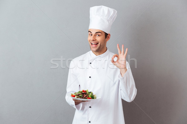 Cook in uniform holding salad showing okay gesture. Stock photo © deandrobot