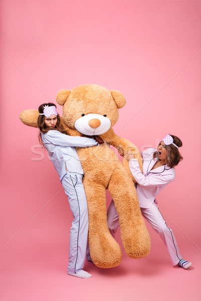 Displeased friends women in pajamas can't divide big teddy bear. Stock photo © deandrobot