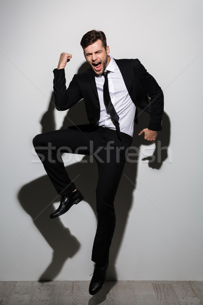 Full length photo of overjoyed handsome guy in black suit showin Stock photo © deandrobot