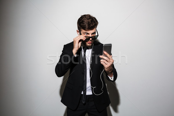 Portrait of a shocked young man in suit and tie Stock photo © deandrobot