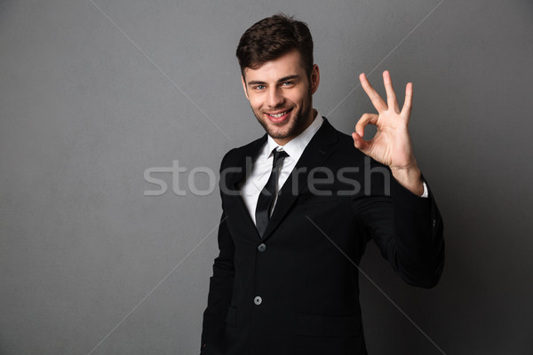 Handsome businessman in black suit showing OK gesture, looking a Stock photo © deandrobot