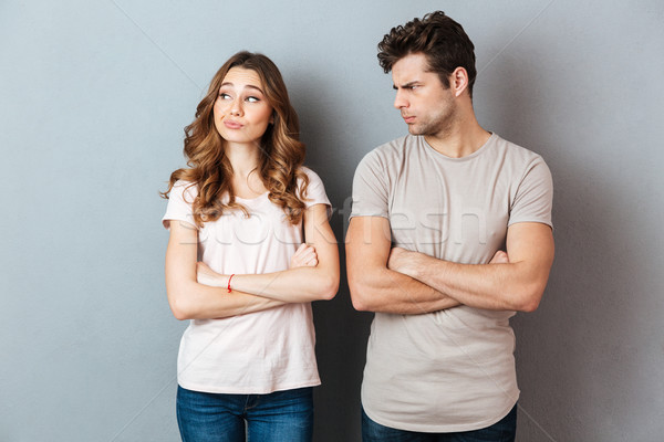 Disappointed young couple standing with arms folded Stock photo © deandrobot