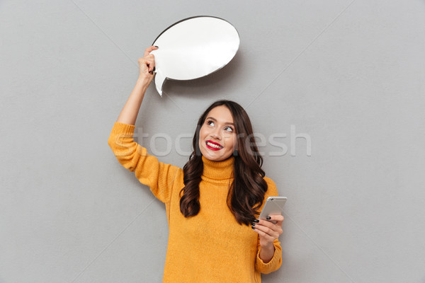Smiling pensive woman in sweater with blank speech bubble overhead Stock photo © deandrobot