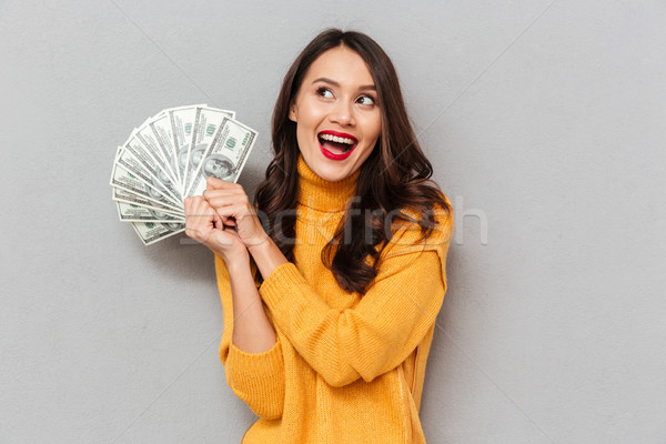 Cheerful brunette woman in sweater holding money and looking up Stock photo © deandrobot