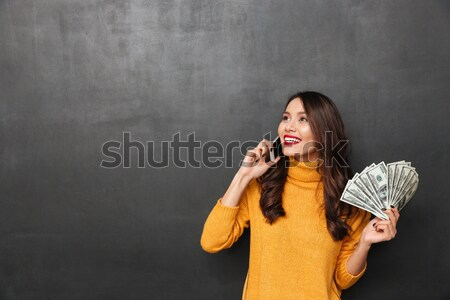 Happy brunette woman in sweater holding money and rejoices Stock photo © deandrobot