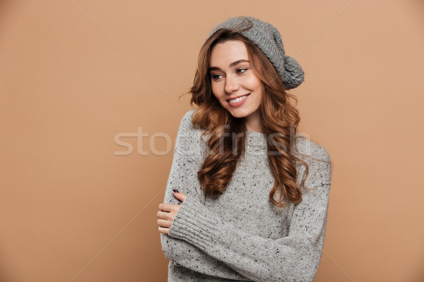 Joyful brunette girl in gray knitted sweater and hat keeping han Stock photo © deandrobot