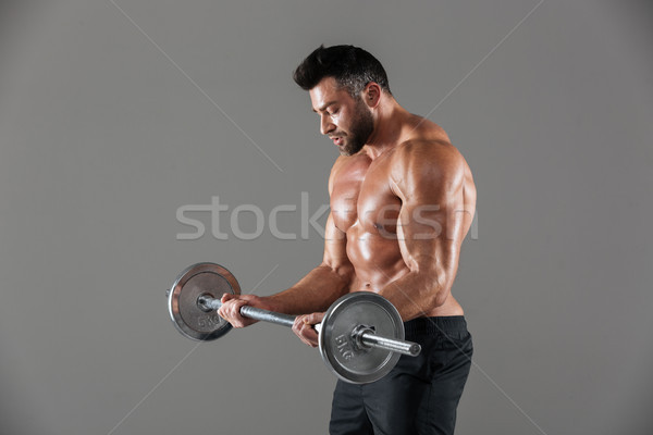 Side view of a concentrated strong shirtless male bodybuilder Stock photo © deandrobot