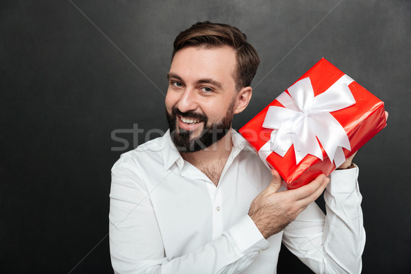 Portrait of curious man shaking red box gift wrapped, and trying Stock photo © deandrobot