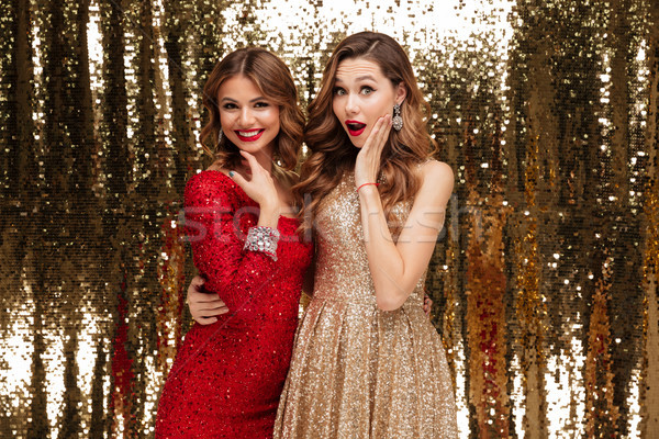 Portrait of two smiling excited women in sparkly dresses Stock photo © deandrobot